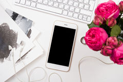 Smartphone, computer keyboard and fesh pink flowers on white tab Stock Photo