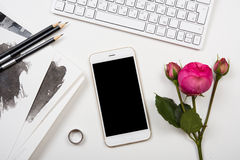 Smartphone, computer keyboard and fesh pink flowers on white tab Stock Image