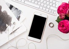 Smartphone, computer keyboard and fesh pink flowers on white tab Stock Photos