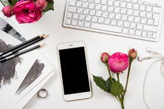 Smartphone, computer keyboard and fesh pink flowers on white tab Stock Images