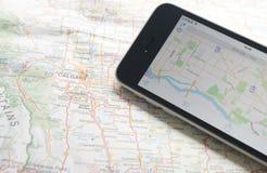 Smartphone con el navegador del GPS en correspondencia Imagenes de archivo