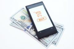 Smartphone con el uso en línea de las compras en una pantalla y dólares En el fondo blanco Foto de archivo libre de regalías