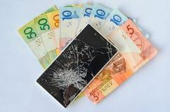 Smartphone con esposizione rotta che si trova sulle banconote dei soldi su un fondo bianco Immagini Stock