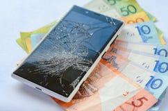 Smartphone con esposizione rotta che si trova sulle banconote dei soldi su un fondo bianco Fotografia Stock