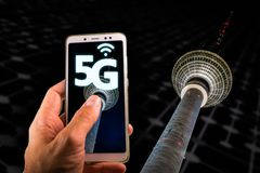 Smartphone con 5G en la pantalla y la torre famosa de la televisión de Berlín o Fernsehturm en el fondo fotografía de archivo libre de regalías