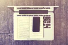 Smartphone con il libro ed il computer portatile su una tavola di legno Immagine Stock