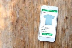 Smartphone con il sito Web dello schermo di commercio elettronico su fondo di legno Immagini Stock Libere da Diritti