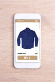 Smartphone con il sito Web dello schermo di commercio elettronico su fondo di legno Fotografia Stock Libera da Diritti