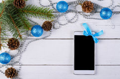 Smartphone con la decoración de la Navidad en una tabla blanca, de arriba Imagen de archivo