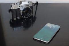 Smartphone con la exhibición completa de la cubierta contra una cámara digital Imagen de archivo libre de regalías
