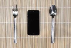 Smartphone con la forchetta ed il cucchiaio sul fondo di bambù della stuoia Fotografie Stock Libere da Diritti