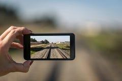 Smartphone con la foto del ferrocarril Fotografía de archivo