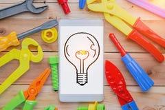 Smartphone con la lampadina e gli strumenti pratici Immagine Stock
