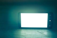 Smartphone con la pantalla blanca en un fondo de madera Fotos de archivo libres de regalías