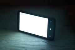 Smartphone con la pantalla blanca en un fondo de madera Imagenes de archivo