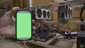 Smartphone con la pantalla de visualización verde al lado del aparejo minero del cryptocurrency sostenido por código que mecanogr metrajes