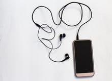 Smartphone con la pantalla en blanco conecta con los auriculares con el cable espiral en la opinión superior del fondo blanco fotografía de archivo libre de regalías