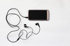 Smartphone con la pantalla en blanco conecta con los auriculares con el cable espiral en la opinión superior del fondo blanco foto de archivo libre de regalías