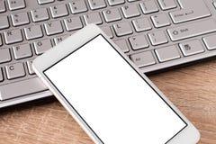Smartphone con la pantalla en blanco en el teclado Fotos de archivo libres de regalías