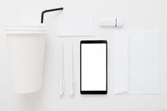 Smartphone con la pantalla en blanco y la materia de la oficina Fotografía de archivo libre de regalías