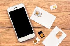 Smartphone con la pantalla en blanco y las tarjetas de SIM Foto de archivo libre de regalías