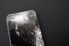 Smartphone con la pantalla quebrada en fondo oscuro Foto de archivo