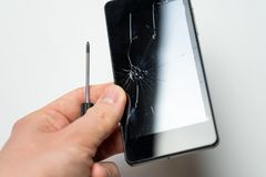 Smartphone con la pantalla y el destornillador quebrados en mano para hombre delante del fondo blanco imagenes de archivo