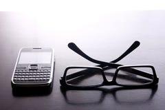 Smartphone con la tastiera di qwerty e le paia degli occhiali Immagini Stock