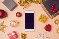 Smartphone con las decoraciones de la Navidad Mofa de la Navidad encima de la plantilla Visión desde arriba Imagenes de archivo