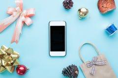 Smartphone con las decoraciones de la Navidad Mofa de la Navidad encima del templat Fotos de archivo libres de regalías