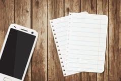 Smartphone con las hojas de papel Imagenes de archivo
