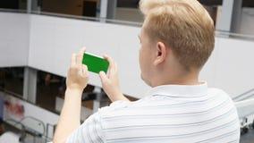 Smartphone con las manos masculinas de la pantalla verde que juegan a un juego en modo de paisaje Pantalla verde adaptable fácil  almacen de video