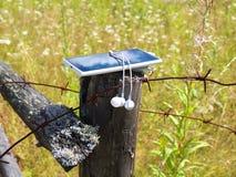 Smartphone con le cuffie sul palo invecchiato Fotografie Stock Libere da Diritti