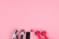 Smartphone con lo schermo in bianco e l'attrezzatura di forma fisica isolati sul rosa Immagini Stock