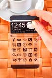 Smartphone con lo schermo trasparente in mani umane Immagine Stock