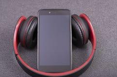 Smartphone con los auriculares del bluetooth a escuchar la música foto de archivo