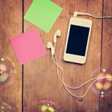 Smartphone con los auriculares y las notas pegajosas sobre superficie de madera Fotos de archivo libres de regalías