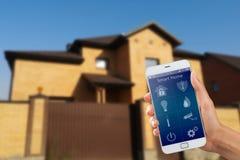 Smartphone con sicurezza domestica app in una mano sui precedenti della costruzione Fotografie Stock Libere da Diritti