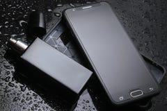 Smartphone con un caso protettivo, una bottiglia di men' profumo di s fotografia stock