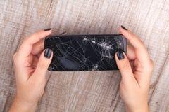 Smartphone con una pantalla quebrada en la mano del ` s de la muchacha Imágenes de archivo libres de regalías