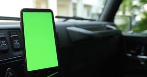 Smartphone con una pantalla verde en el coche almacen de metraje de vídeo