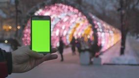 Smartphone con una pantalla verde En el fondo, las guirnaldas coloreadas del Año Nuevo están desenfocado metrajes