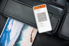 Smartphone conectó con la impresora inalámbrica de la foto Fotografía de archivo