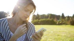 Smartphone conmovedor de la mujer joven foto de archivo