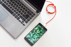 Smartphone is connecting to laptop computer close-up.  Royalty Free Stock Photography