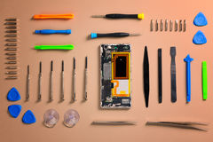 Smartphone cover removed, internals exposed with tools arranged around. Royalty Free Stock Image