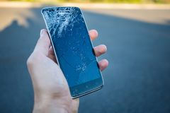 A smartphone with a cracked screen. Men`s hands hold a smartphone with a cracked screen stock photography