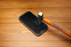 Smartphone crushed by hammer Royalty Free Stock Photos