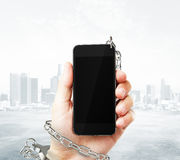 Smartphone cuffed to hand Royalty Free Stock Photography