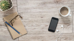 Smartphone, cuffie, taccuino e caffè su fondo di legno Fotografie Stock Libere da Diritti